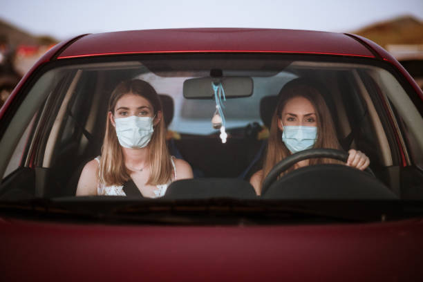Two women wearing face masks inside a car stock photo
