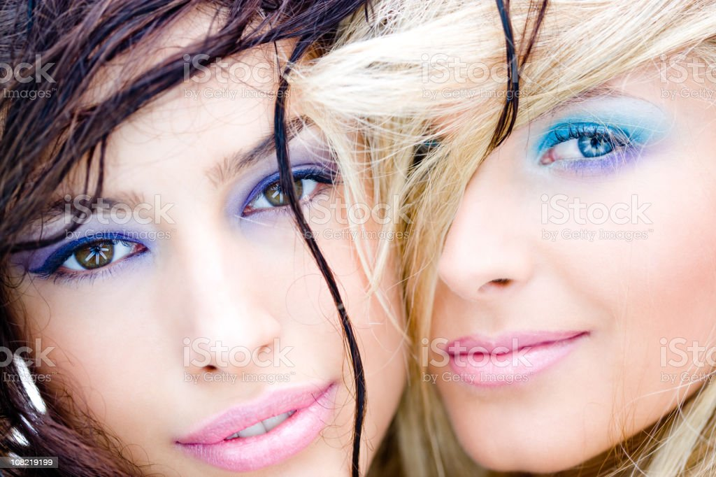 Two Women Wearing Make-Up and Smiling Close Together stock photo