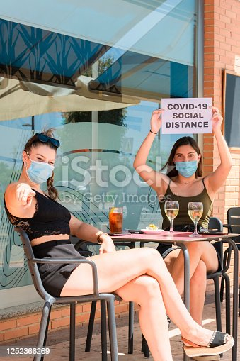 Two women wearing surgical masks and sitting at an outdoor terrace, one of them holding a sign with a safety message over her head while the other points at the camera. Social distancing concept.