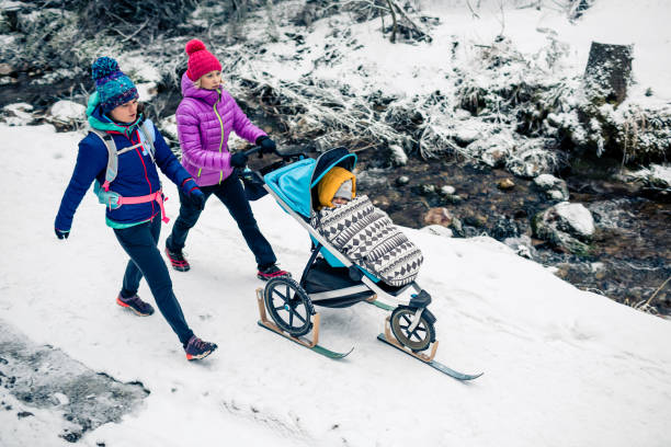 Two women with baby stroller enjoying winter in forest, family time stock photo