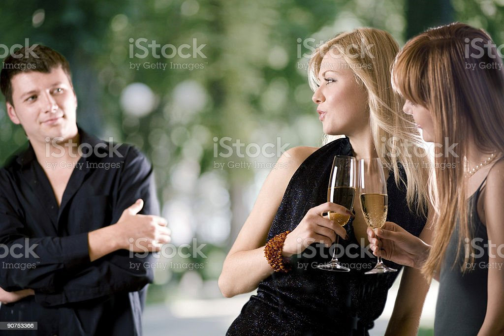 Two women with champagne looking at man at an elegant party stock photo