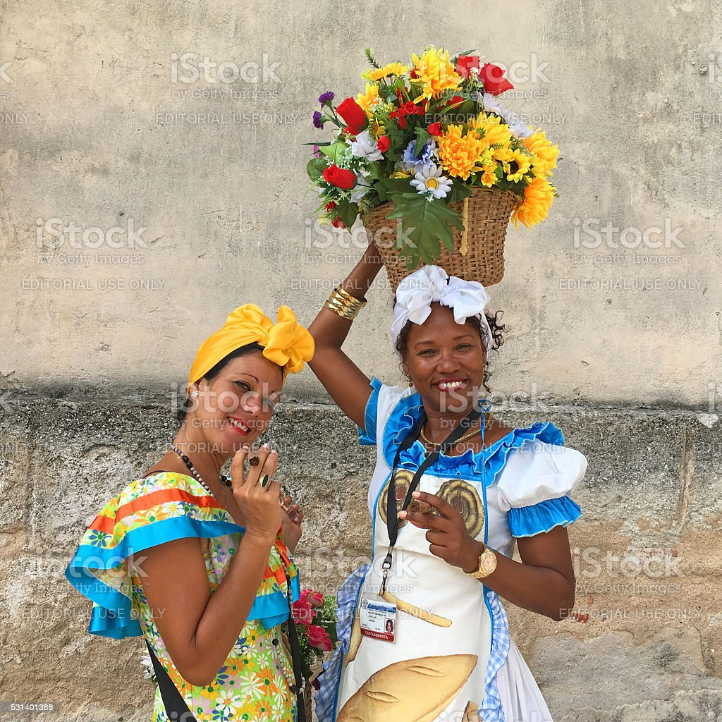 Two women with cigars Havana, Cuba - April 26, 2016: Two young cuban women with cigars, one of them with the basket full of colorful artificial flowers posing for the picture, Havana, Cuba. Adult Stock Photo