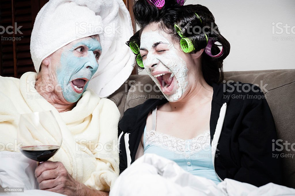 Two women with drying beauty face masks stock photo