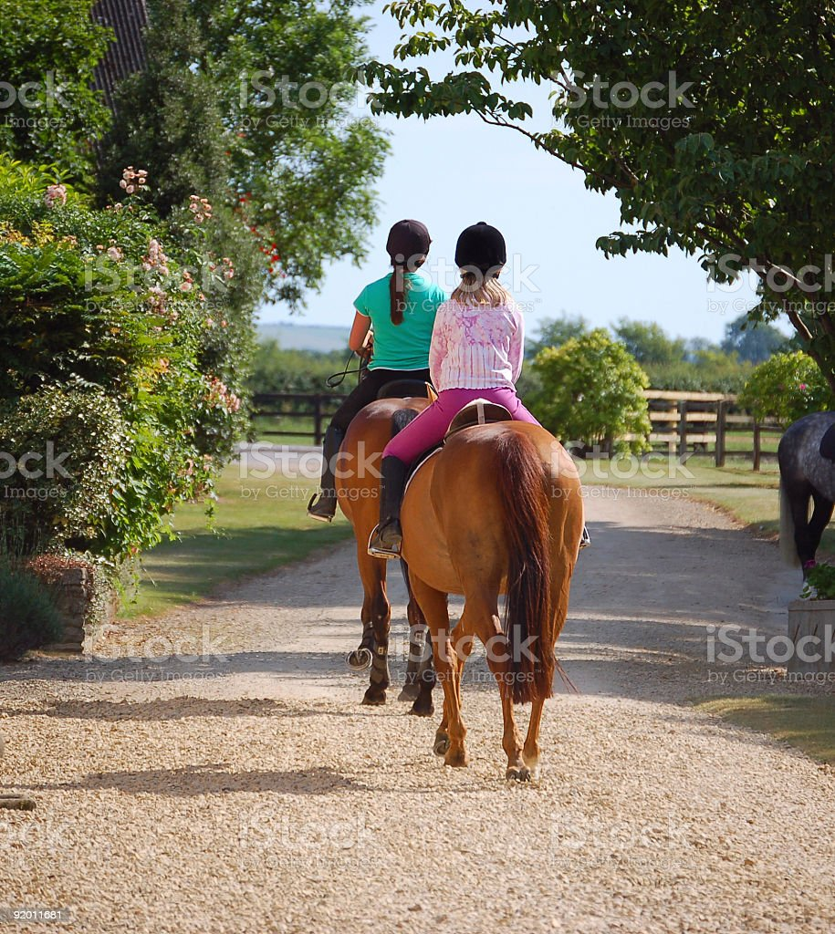Two women with horses riding in the countryside stock photo