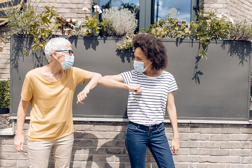 Two neighbors wearing protective face masks, meeting on the street and greeting with their elbows.