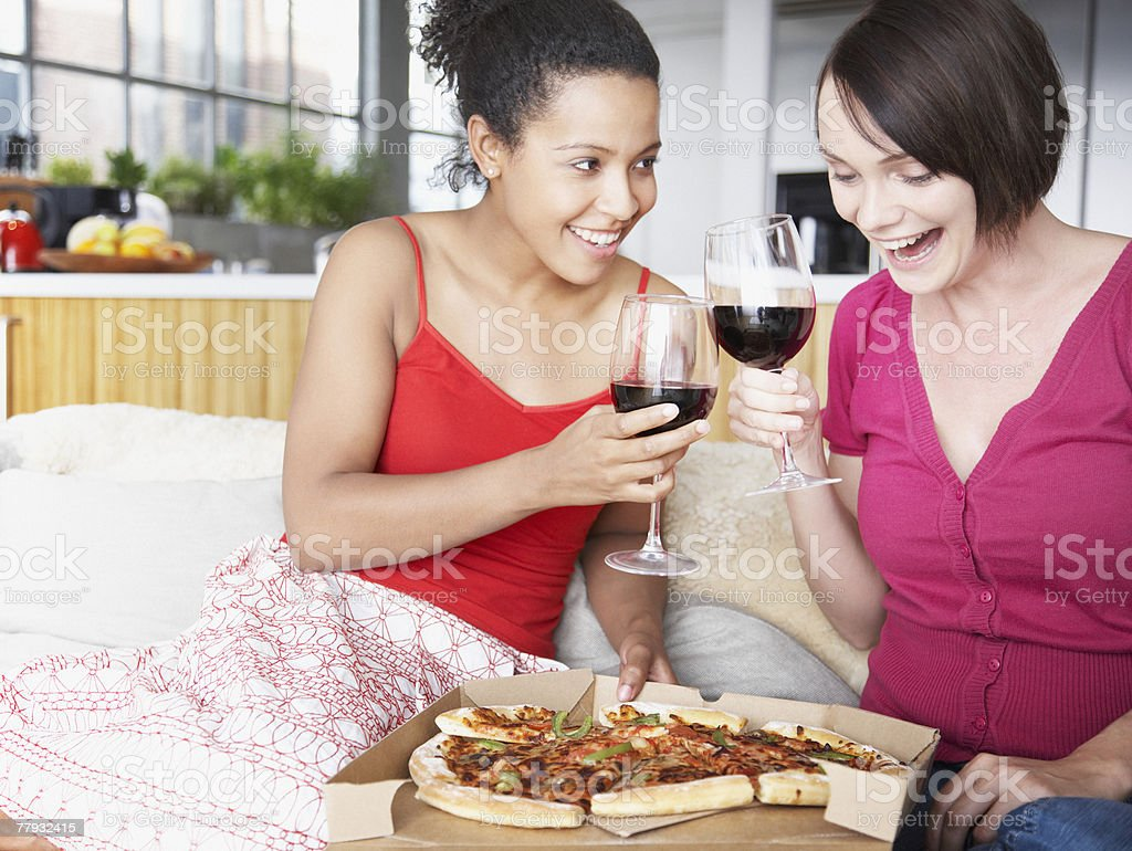 Two women with wine and pizza in a living room royalty-free stock photo