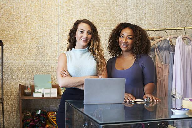 two women working in clothing store looking to camera - kleidung amerikanischer ureinwohner stock-fotos und bilder