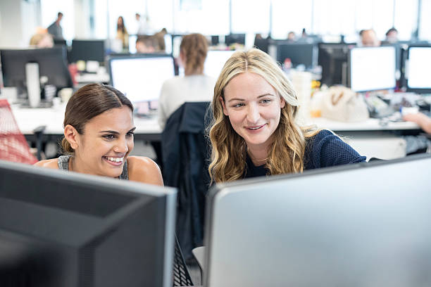 Two women working in office looking at computer, smiling stock photo