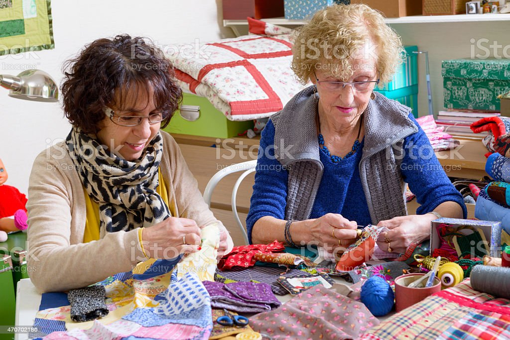 two women working on their quilting stock photo