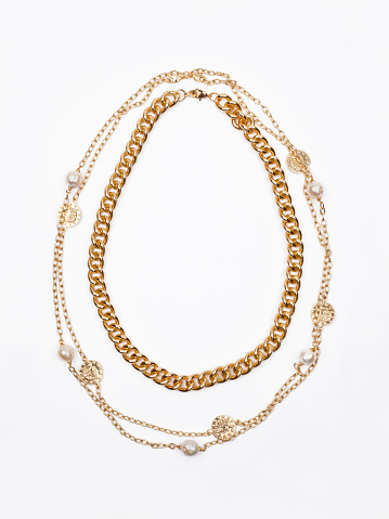 Two women`s gold necklaces on white background. Top view