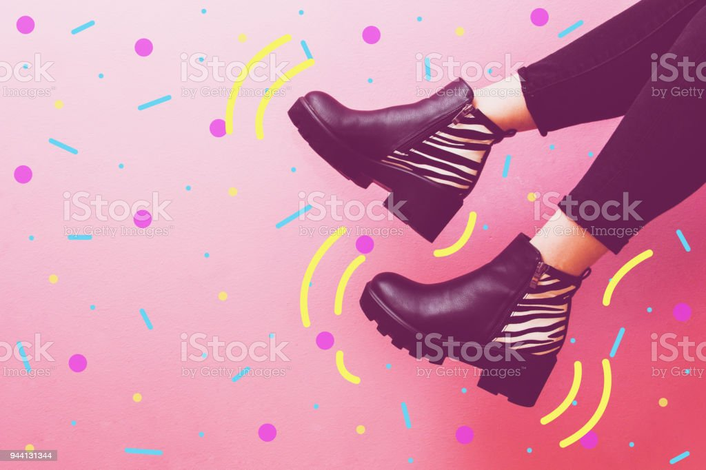 two women's legs dangle in fashionable boots. stock photo