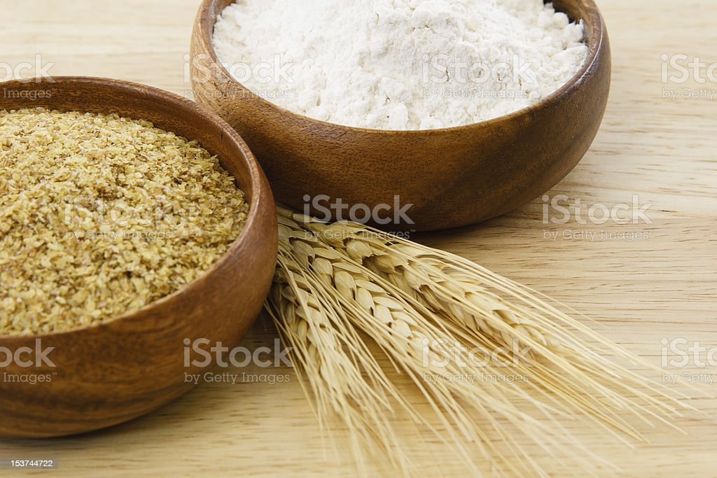 Two wood bowls with flour and wheat germ stock photo