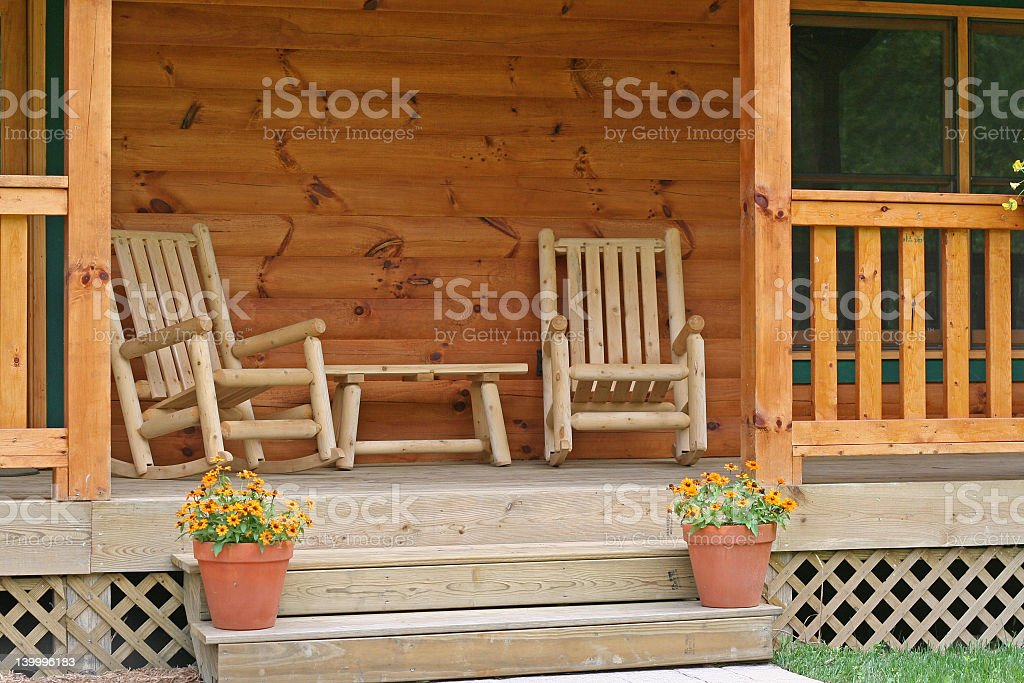 Two wood rocking chairs on a porch with flowers on the steps stock photo
