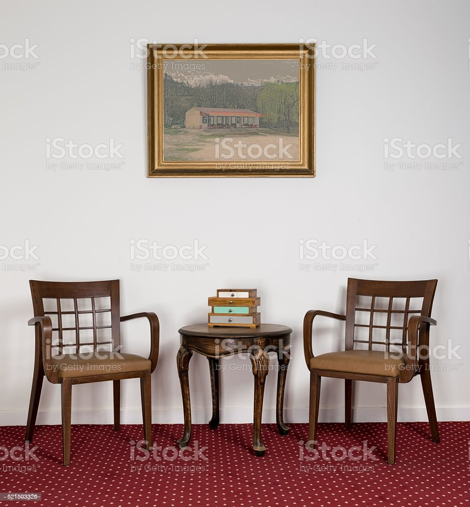 Two wooden armchairs, small round coffee table and framed painting stock photo