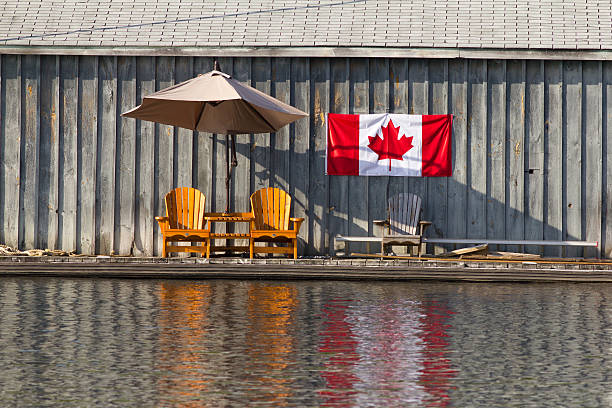 two wooden chairs and canadian flag - canada day stock pictures, royalty-free photos & images
