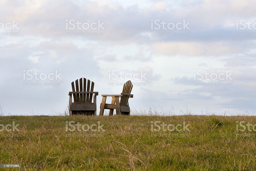 Two wooden chairs in a field with sky. stock photo