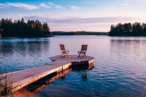 Two wooden chairs on a wood pier overlooking a lake at sunset