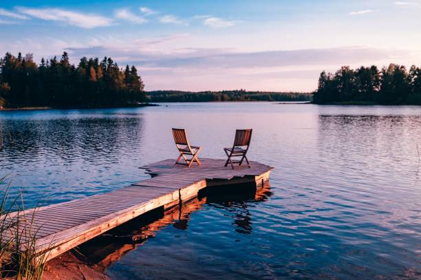 Two wooden chairs on a wood pier overlooking a lake at sunset stock photo