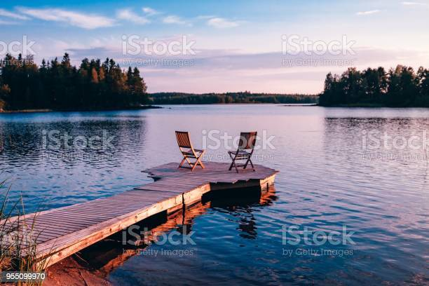 Photo of Two wooden chairs on a wood pier overlooking a lake at sunset