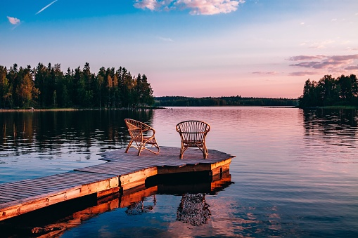 Two Wooden Chairs On A Wood Pier Overlooking A Lake At