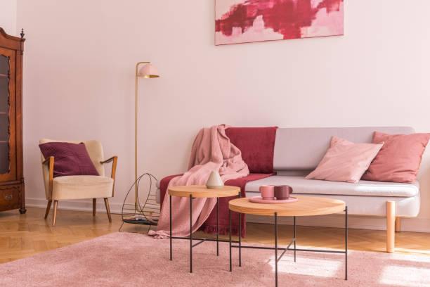 Zwei hölzerne Couchtische neben einem modernen grauen Sofa mit Kissen und Decken in hübscher pastellrosa Wohnzimmereinrichtung – Foto