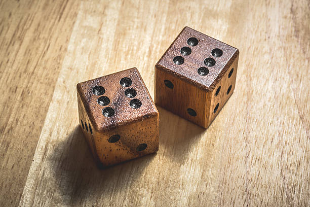 two wooden dice with the number 6 on a table. - symmetrie stock-fotos und bilder