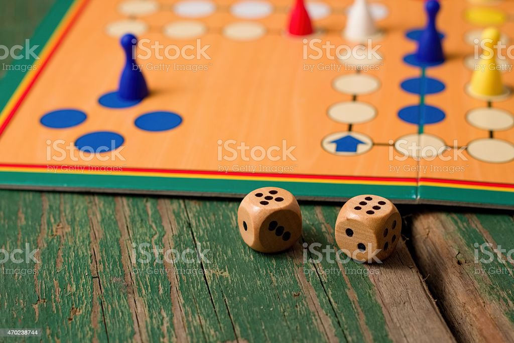 Two wooden dices in front of ludo with figurines stock photo