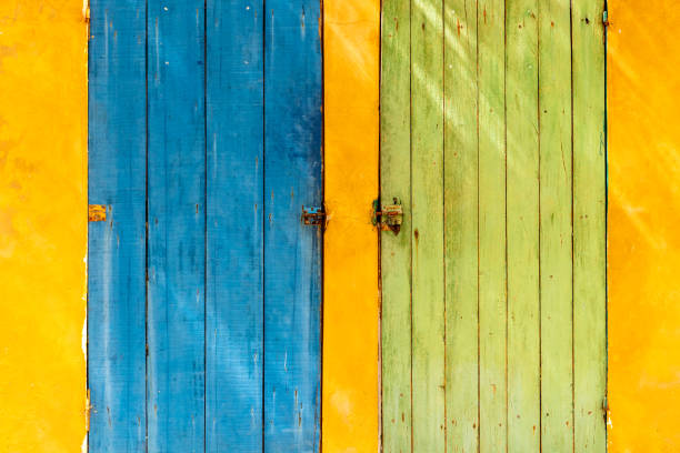 Two wooden doors in a brightly colored wall in Senegal stock photo