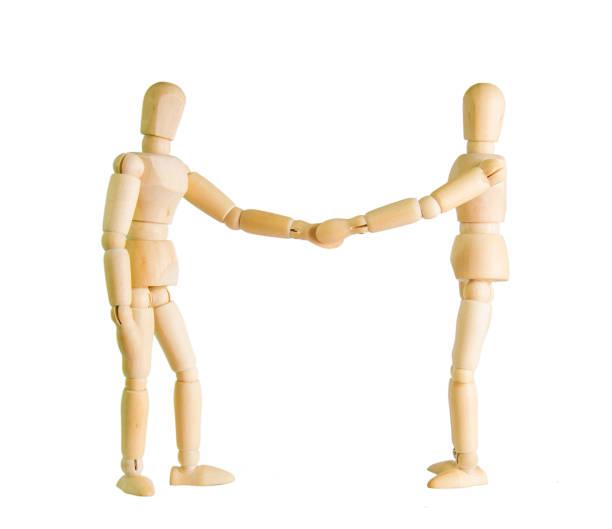 Deux poupées en bois figure faisant une poignée de main sur un fond blanc - Photo