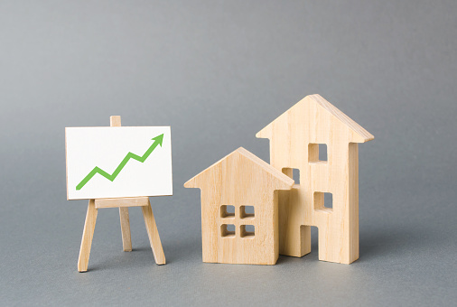 831745600 istock photo Two wooden houses and a green up arrow on the sign. Real estate value increase. Rising prices for housing, building maintenance. High rates of construction, high liquidity. Supply and demand 1161032653