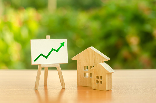 istock Two wooden houses and stand with green up arrow. Increasing cost and liquidity of real estate. Attractive investing. rising prices or renting. Apartments and apartments. Sales rate. Supply and demand 1162400945