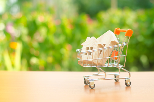 831745600 istock photo Two wooden houses in a trading cart on nature background. The concept of buying and selling real estate, renting. Attractive investing. rising prices. supply and demand, rates of sales 1161032656