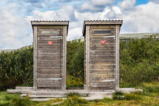 Two wooden outhouse toilets with red heart in mountain landscape. stock photo