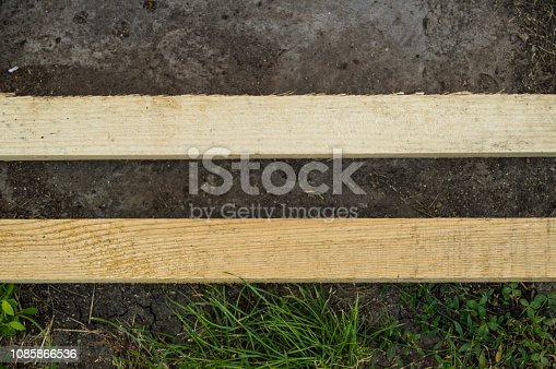 istock Two wooden planks lie parallel on the ground and grass in the garden 1085866536