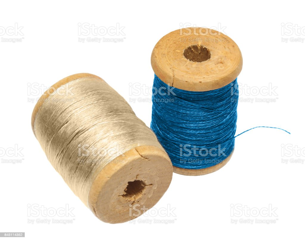 two wooden spool threads from the blue and the beige threads on a white backdrop stock photo