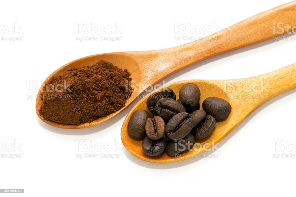 Two wooden spoons filled with coffee beans and ground coffee stock photo