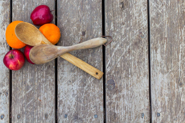 Two Wooden Spoons on Apples and Oranges stock photo
