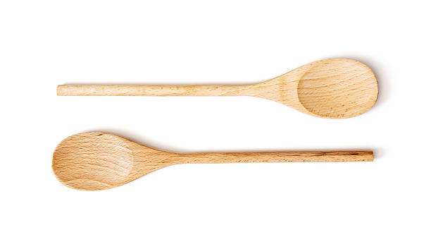 two wooden spoons on the white background - lepel stockfoto's en -beelden