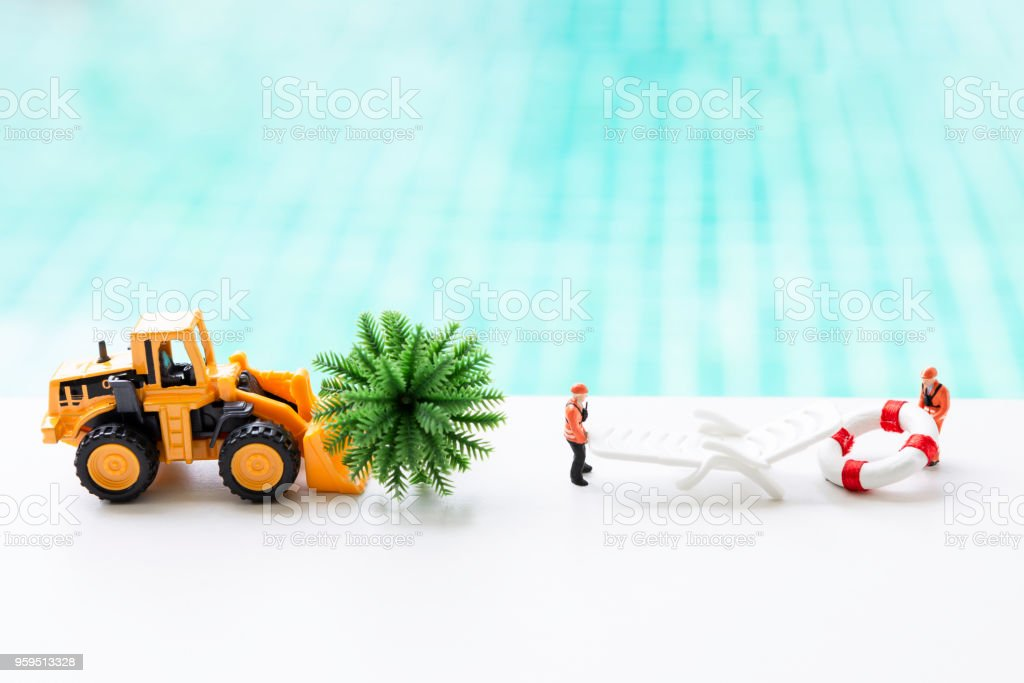 Two worker moving life buoy and beach chair with front loader truck moving coconut tree stock photo