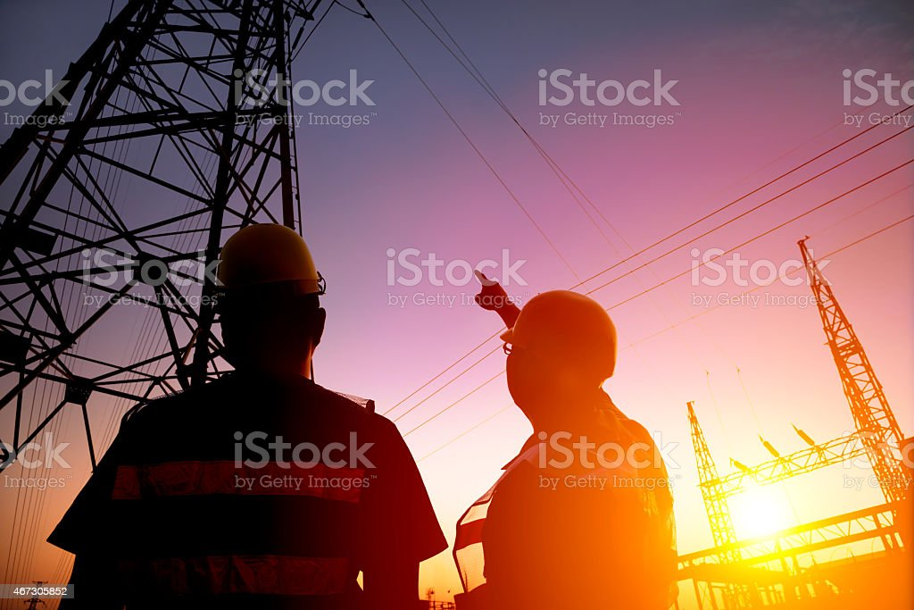 two worker watching the power tower and substation two worker watching the power tower and substation with sunset background 2015 Stock Photo