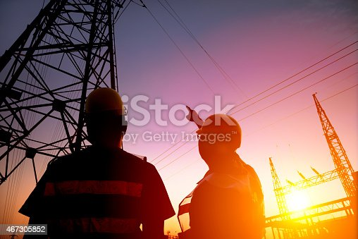 two worker watching the power tower and substation with sunset background