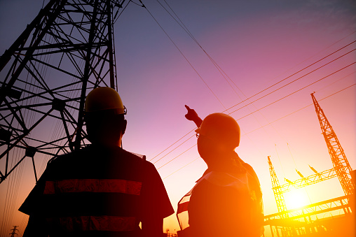 Two Worker Watching The Power Tower And Substation Stock Photo - Download Image Now