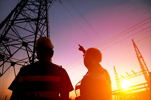 two worker watching the power tower and substation two worker watching the power tower and substation with sunset background power occupation stock pictures, royalty-free photos & images