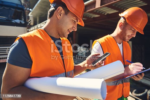 Waist up of two employees standing near the building while one of them holding smartphone