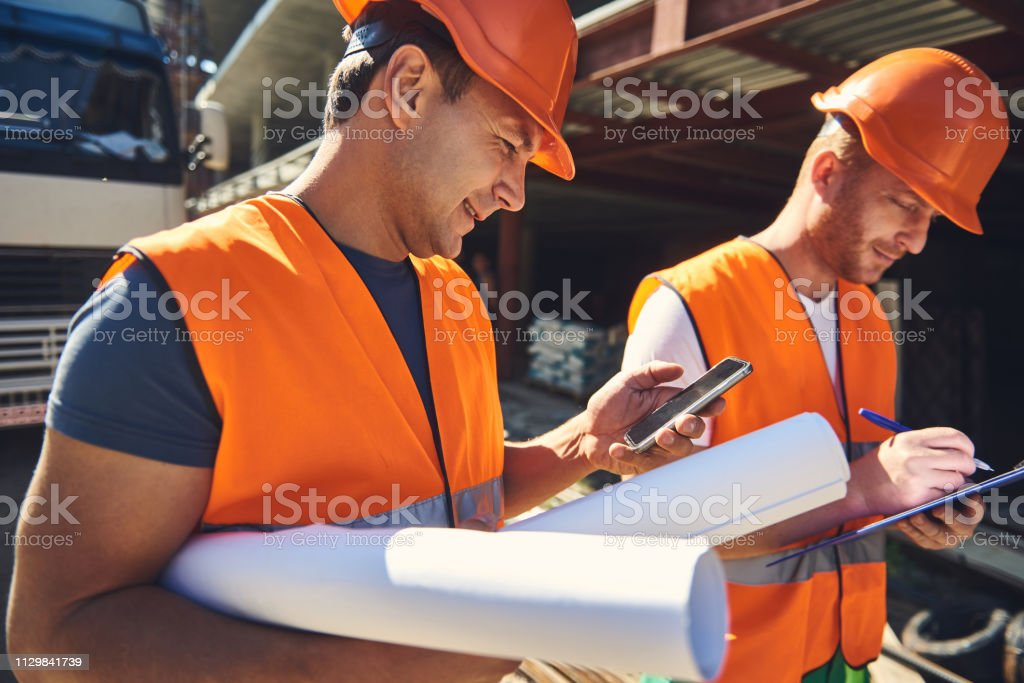 Two workers are walking near construction site stock photo
