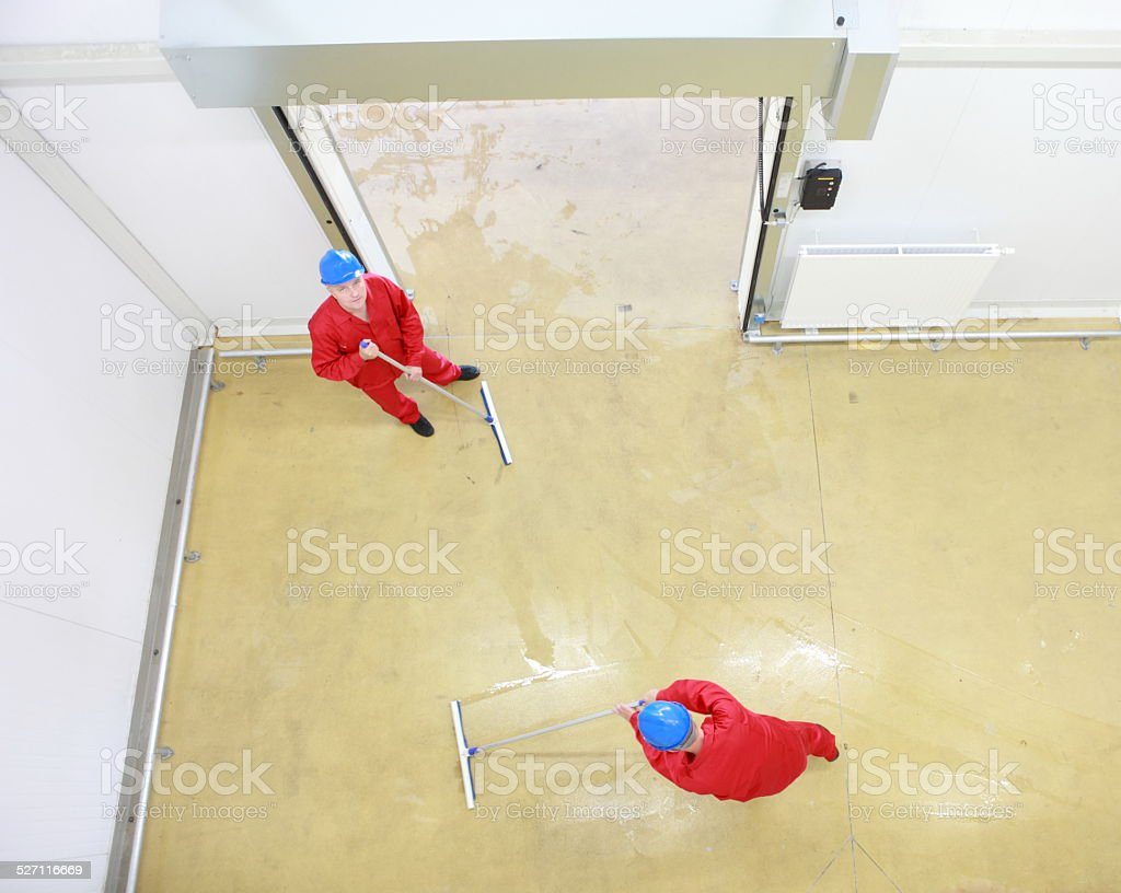 two workers cleaning floor in industrial building stock photo