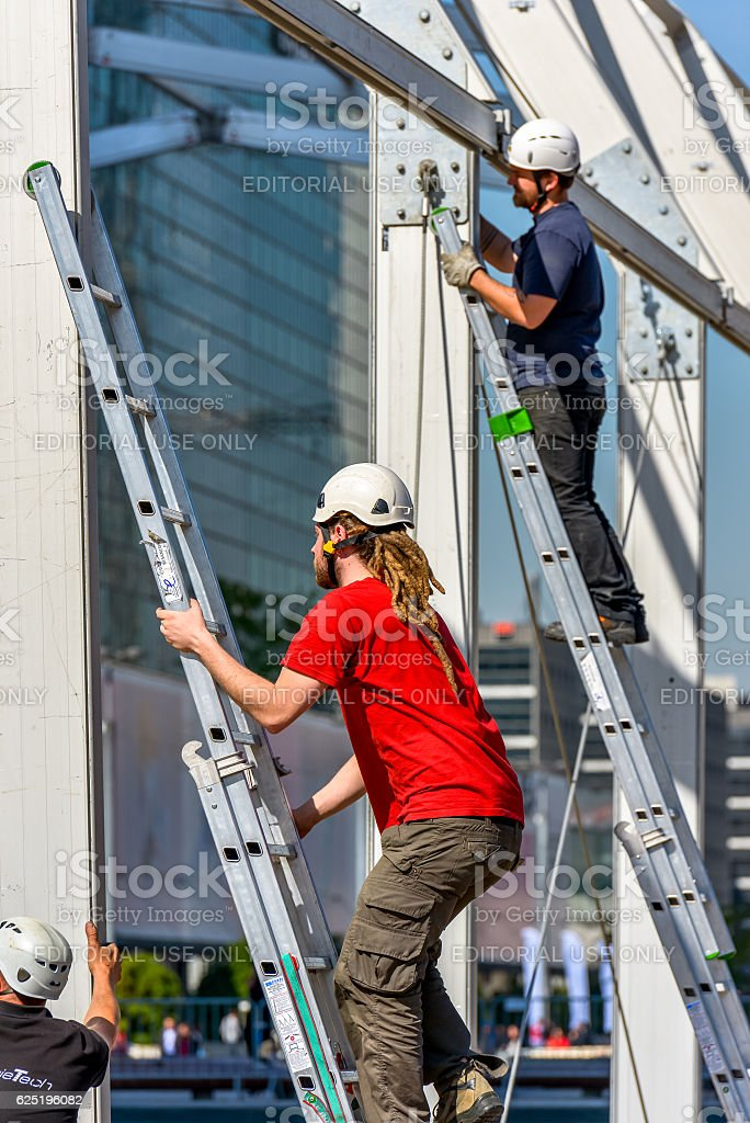 Two workers climbing on metal ladders on a construction site stock photo