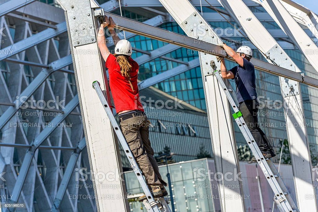 Two workers climbing on metal ladders stock photo