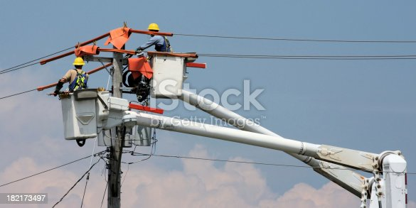 Hydro workers work from boom buckets to restore power to a community. 2 to 1 aspect.