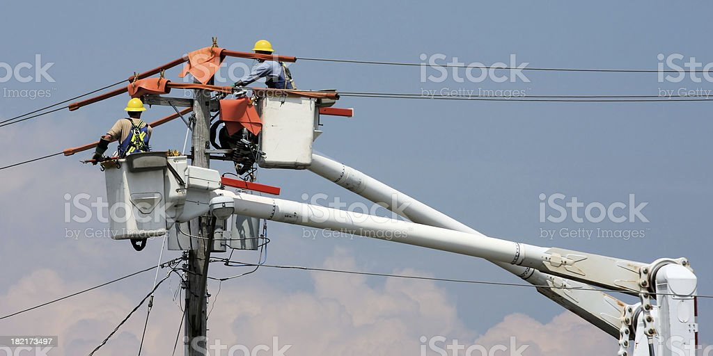 Two workers in a crane repairing a power pole stock photo